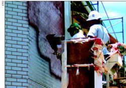 A very large amount of decorative thin overlay work is installed every year. Workers here are using a hopper gun to spray colored overlay cement over paper running bond brick stencils.