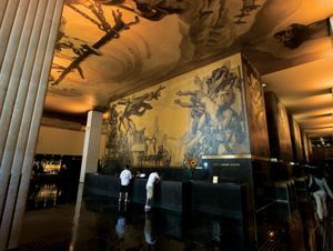 """One of Abe Feder's most significant projects was the lighting of the lobby murals at Rockefeller Center in New York. Fixtures were painted to blend into the walls and to illuminate the 1930s artwork, """"New Frontiers,"""" by José María Sert and Frank Brangwyn."""