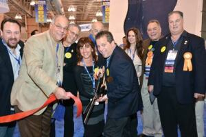 Show Chairman/NESPA Vice President Kyle  Chaikin (with scissors) kicks off the event with a ceremonial  ribbon cutting. He is joined by (L-R) Past President Rob Romano;  Treasurer John C. Migliaccio; APSP President Steve Gorlin; Long  Island Chapter Administrator Karen Pinto; immediate Past President  Clive Ensher; Nataliya Romano; APSP regional Director John Romano;  and President Robert Blanda.