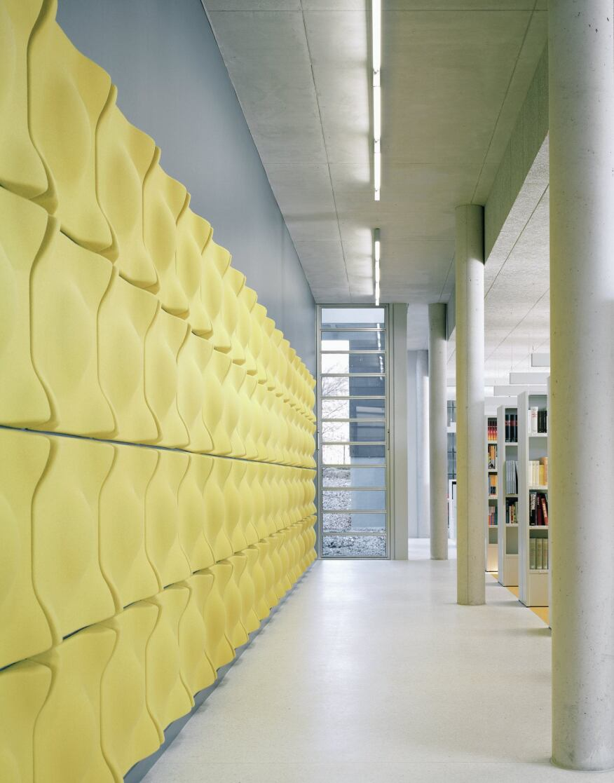 Throughout the concrete-and-glass interior—in the assembly hall, the library (shown), and the multipurpose rooms—the architects used Soundwave Swell modular acoustic panels from Offecct to dampen sound. Designed by Teppo Asikainen of Helsinki-based Valvomo Architects, the panels are formed from molded recyclable polyester fiber and covered in Europost fabric from Gabriel. The library stacks, manufactured by Bruynzeel, are starkly white in keeping with the building's overall aesthetic.