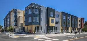 The flat-style and townhouse apartments wrap around center courtyards to provide private outdoor space and are built over at-grade parking structures. All phases have a certification goal of LEED Gold.