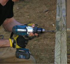 Figure 5. A heavy-duty drill and an auger bit make quick work of the bolt holes. The author drills 3/4-inch holes for 1/2-inch bolts to provide flexibility for shimming the post plumb.