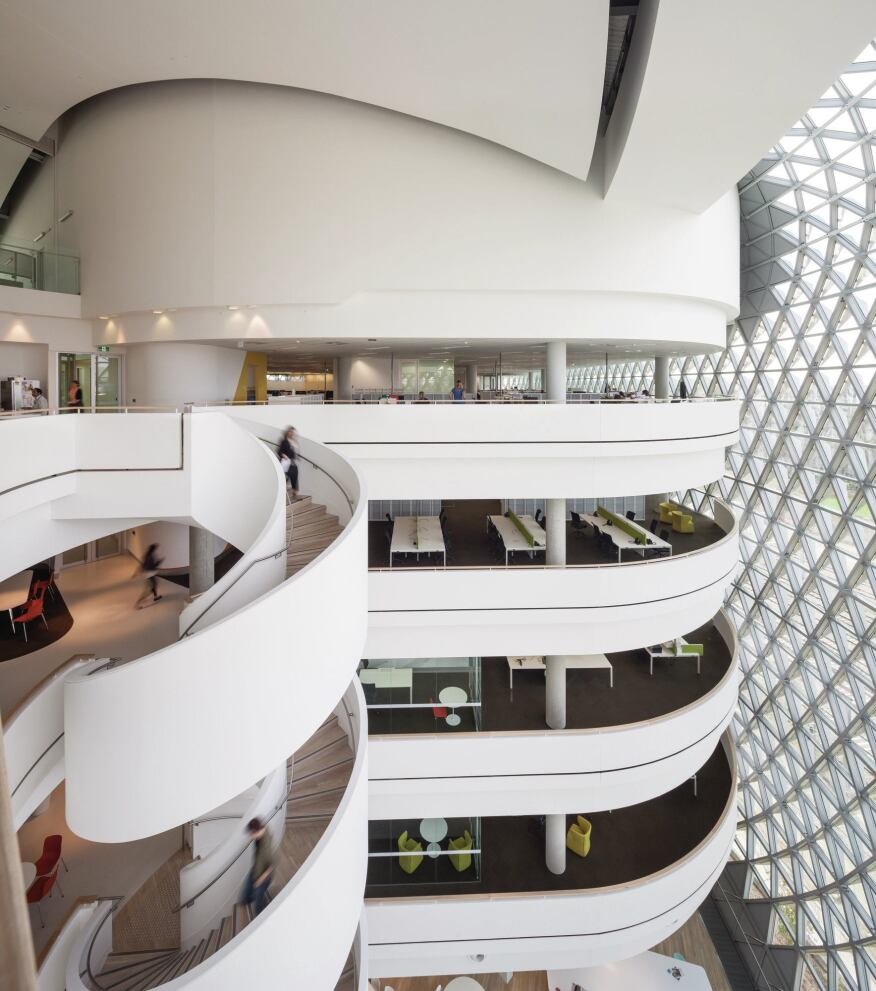 The east atrium is bigger than the one on the west, largely because of its reduced solar exposure, which allows for a more comfortable interior environment. Write-up spaces open onto the atrium, and a spiral staircase connects floors.