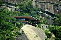 This African House is Perched on the Edge of a Rocky Slab