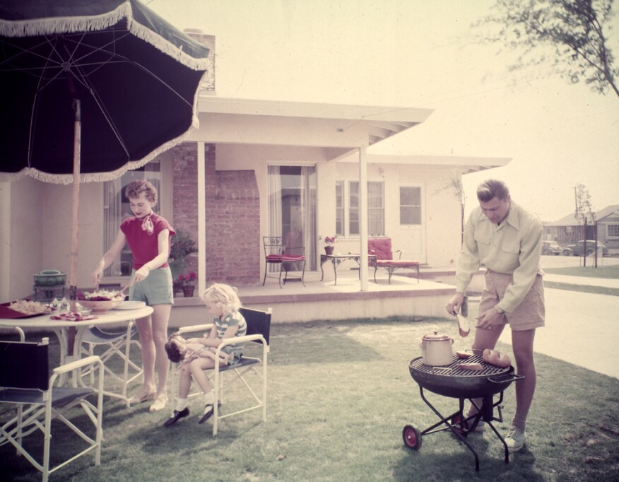 A family enjoying a barbecue in their backyard.