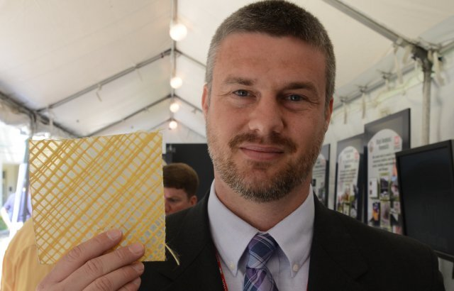 U.S. Army Corps' research mechanical engineer Nick Boone with a piece of the ballistic wallpaper.