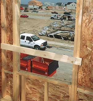 Nail 2x4 guardrails across window openings as soon as walls are erected.