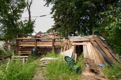 Materials hand-salvaged from the existing house are stored in the backyard of the neighboring farmhouse.