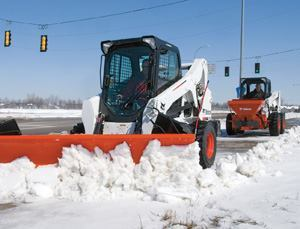 These two skid-steer loaders are working together to clear snow and spread salt on a pedestrian walkway. Photo: Bobcat Co.