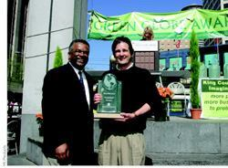 John Ackerman (right) accepts a Green Globe award last year from King County executive Ron Sims on behalf of YK Products LLC.