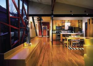 A splurge on Brazilian cherry flooring underscores the kitchen zone within the larger, maple-floored room.