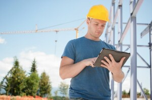 Construction worker looking at blueprints on digital tablet