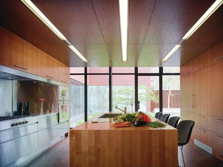 In the ground-floor kitchen, appliances from Gaggenau and Sub-Zero are set into custom cabinets fabricated by Stay Straight Manufacturing, the same company that made the perforated wood-veneer acoustical ceiling panels. In the center island, a Mila sink is outfitted with a faucet from KWC.