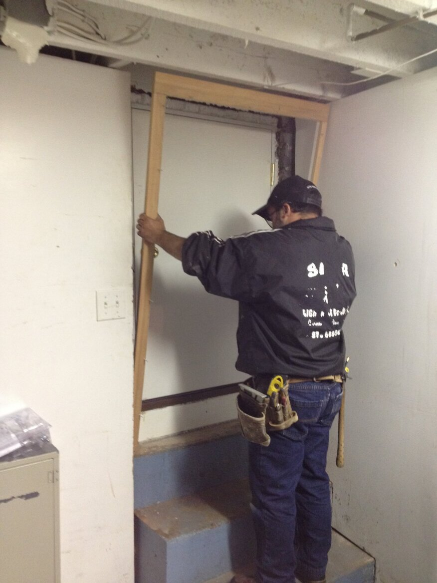 Before the foam insulation solidifies, the pre-assembled interior trim is set in place and nailed to the jambs. It fits between the sides of the opening and helps to keep the foam from expanding out past the door jamb.