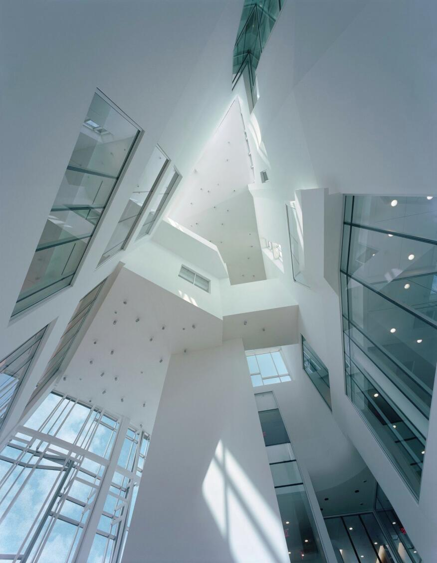 A view toward the top of the central atrium shows the bridged connections between departments and the glazed opening that allow the admitted daylight to penetrate deeper into the building's floor plates.