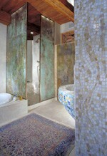 The master bathroom is entered through an arched, mosaic-inlayed doorway flanked by two custom mosaic sinks. Acid-etched glass shower and storage enclosures created by Ginsberg enhance the Byzantine style of this dramatic space.