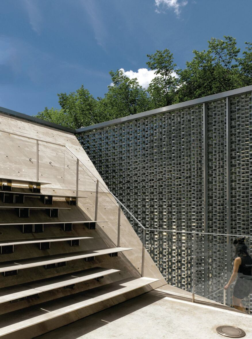 On the second level, the concrete core supports a private stage with metal bleacher seating, accessible via a concrete staircase.