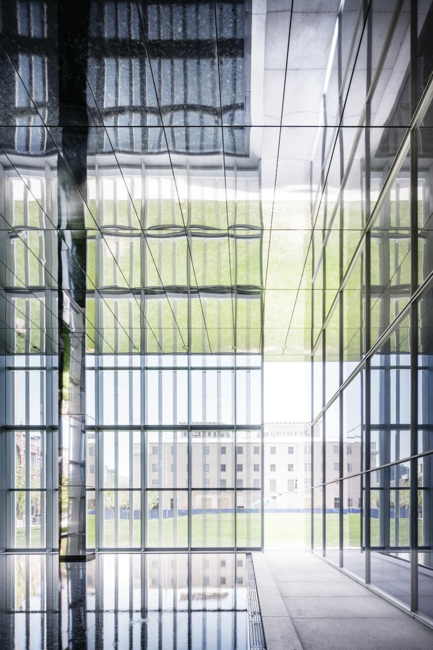 A reflecting pool in the northeast corner of the building is located behind the glass and aluminum skin; a break in the façade opens the space to parkland beyond.