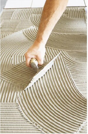 After applying the setting adhesive with the straight edge and bottom of the trowel, the tilesetter combs the setting bed with the trowel held at a 45-degree angle.