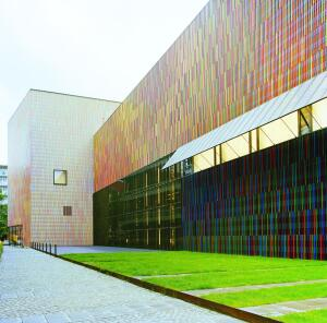 The brightly colored façade of the Brandhorst Museum in Munich is made up of squareprofile ceramic sticks mounted in front of a folded metal cladding. Before pursuing this design, the architects also considered metal fabric, perforated glass, and a perforated ceramic scrim, all of which were rejected for cost or aesthestic reasons.