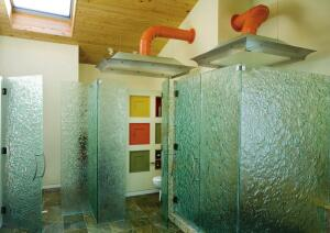 """Next to the master bedroom is the bathroom, where Buckborough used highly textured art glass from California. """"The clients said they wanted to use ëfunky, unique materials,í"""" says Buckborough, who made several partitions from the seemingly undulating glass, which is nearly an inch thick where the glass is most textured. """"It lets light in and itís still private.""""  He cautions that although attractive, the panels were difficult to install because they had to be the exact size and shape specified. Also, he says, there was a long lead time for ordering, since the glass is floated and had to be made on special rubber forms."""