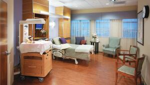 A labor and delivery room at Holmes Regional Medical Center in Melbourne, Fla. The room, designed by HKS, features family seating, an occasional table, and a computer station within the headwall cabinetry.