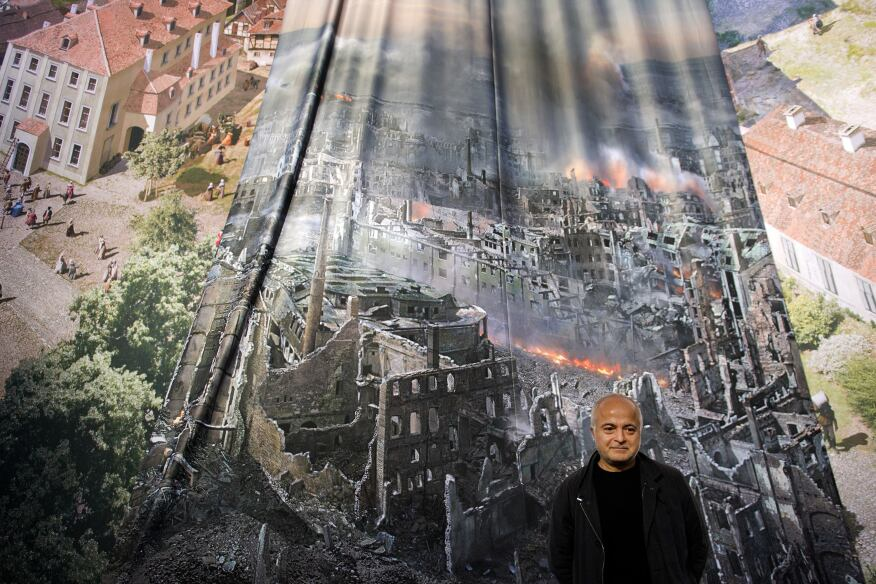 """Artist Yadegar Asisi with a test print of the panorama """"Dresden 1945 – Tragedy and Hope of a European City,"""" which depicts Dresden, Germany, after the city was bombed in Feb. 1945. The installation is from the perspective of the town hall tower. The panorama goes on display at the city's Panometer on Jan. 24."""