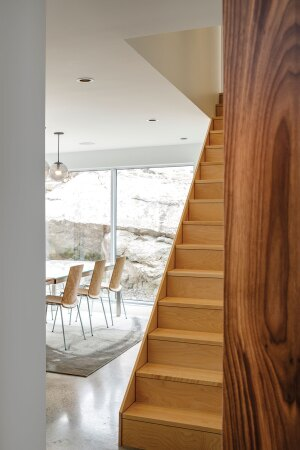 Large boulders visible from the dining room of Float, a residence in Halifax, shelter the house and inspired its fractured volume.