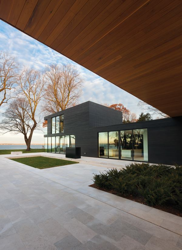 The volume containing the living spaces and master suite is clad in a black-stained cedar rainscreen, which is installed over a moisture barrier from Benjamin Obdyke.
