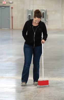 Becky Kazmierski with H.H. Holmes Testing Laboratories uses a D-meter to measure curling in floor panels.