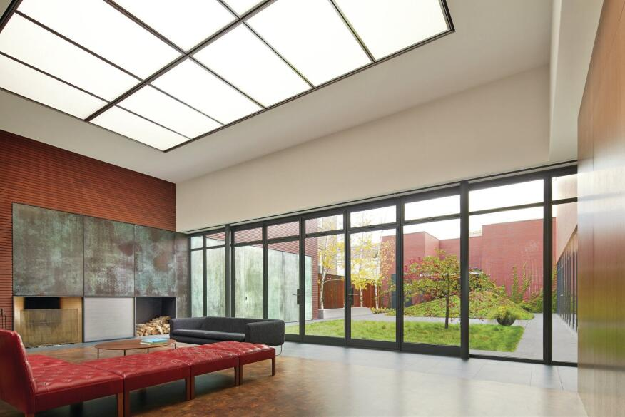 Upon entering the house, the first big space one encounters is a large living room with views out through a system of Hope's steel windows. The fireplace surround is made of the same patinaed copper as the exterior screen. Mesabi Black tiles from Cold Springs Granite are used both inside and out. The red Kaare Klint Addition sofa from Rud Rasmussen sits on Kaswell Walnut end-grain block flooring.