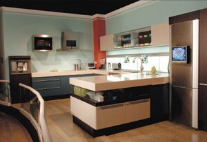 """The House of Innoventions kitchen, which features Poggenpohl's Plusmodo line, includes elements such as open and closed areas with glass pull-out trays and sliding doors, and illuminated satin-glass shelving. A mix of materials is used, including marsh oak wood, lacquer finishes, and aluminum. The 6-inch thick quartz countertop is suspended above four glass pull-out trays. Siemens' futuristic appliances include a ventilation hood with an integrated flat-screen TV and DVD/CD player. A """"lift"""" oven descends at the press of a button, making it easy to place and remove dishes."""