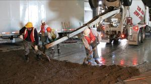 Contractors working for Delta Pacific–Structural Preservation Systems  place an iron aggregate floor topping that's finished just like concrete floors. P