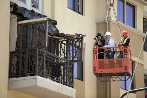 A Berkeley police officer and two engineers in a hanging basket photograph a balcony collapse at an apartment building on Kittredge Street in Berkeley, Calif., Tuesday, June 16, 2015. Six people were killed and seven others were taken to area hospitals. (D. Ross Cameron/Bay Area News Group Archives)