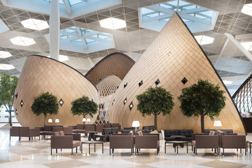 The cocoon lattices are made from laminated layers of solid African ayous wood sourced in Turkey. The enclosed cocoons are clad with polished oak veneer on plywood. Living—artificially stunted—trees burst from the tile floor between the cocoons.