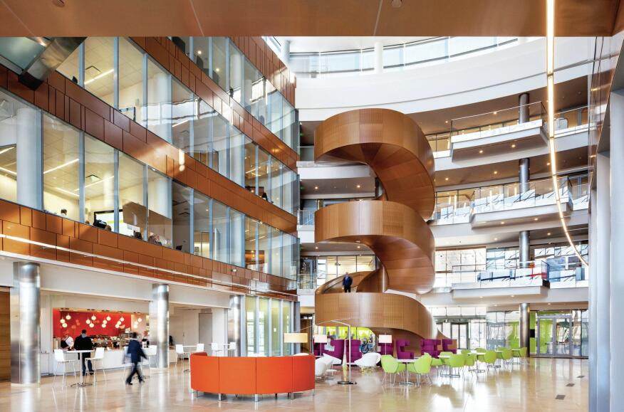 The heart of GSK's offices is four-story central atrium featuring a monumental maple veneer stair. Employees share spaces organized in neighborhoods, along with additional informal seating spaces.