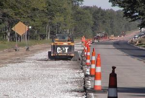 The extra time and materials cost of paving the shoulder was justified by the advantages of keeping two lanes of traffic open throughout construction.