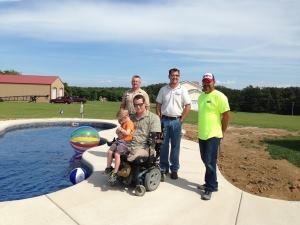 Medically retired Marine Cpl. Justin McLoud and his son Desmond pose by their new pool built by Wideman Pools of Festus, Mo. From left: Dennis Wideman, Rodney Wideman and Doug Ortman, of Ortman Concrete, who donated a portion of the patio.