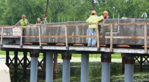 A crew sets a two-piece precast pier cap into position on the Wisconsin State Route 25 Bridge, which bisects the Upper Mississippi National Wildlife and Fish Refuge.