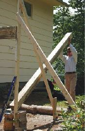 The first joist is run a little long so it can rest on the assistant, while providing space to raise and plumb the post.