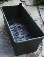 Figure 1. A self-watering container like the one shown above can be easily dropped into a wood frame.