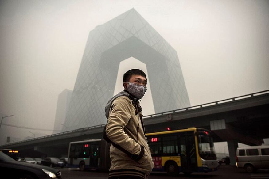 A man wears a mask during heavy smog in Beijing last month. OMA's CCTV building stands in the background.