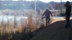 Stormwater foreman Shane Hill (white hard hat) blazes the trail as the crew performs a prescribed burn as part of Lenexa's vegetative management program.