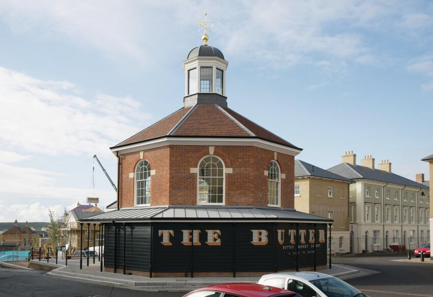 "An octagonal building in the middle of Bridport Road forces drivers to awkwardly skirt the structure—one of many ""events"" that Poundbury's planners use to slow the pace of traffic."