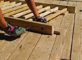 Figure 11. Spreading wood balusters out on pieces of 1-inch-thick decking centers them perfectly on 2x4 rails. An impact driver makes quick work of the 3 1/2-inch screws that join the parts.
