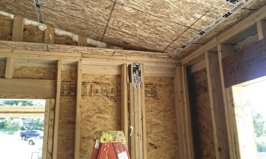 A horizontal strip of OSB at wall-plate height tied the inner wall frame to the outer frame.
