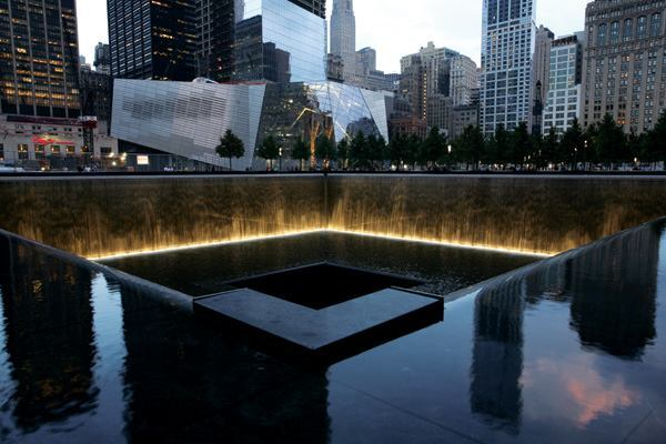 A view of the North Tower Reflecting Pool with the National September 11 Museum in the background.