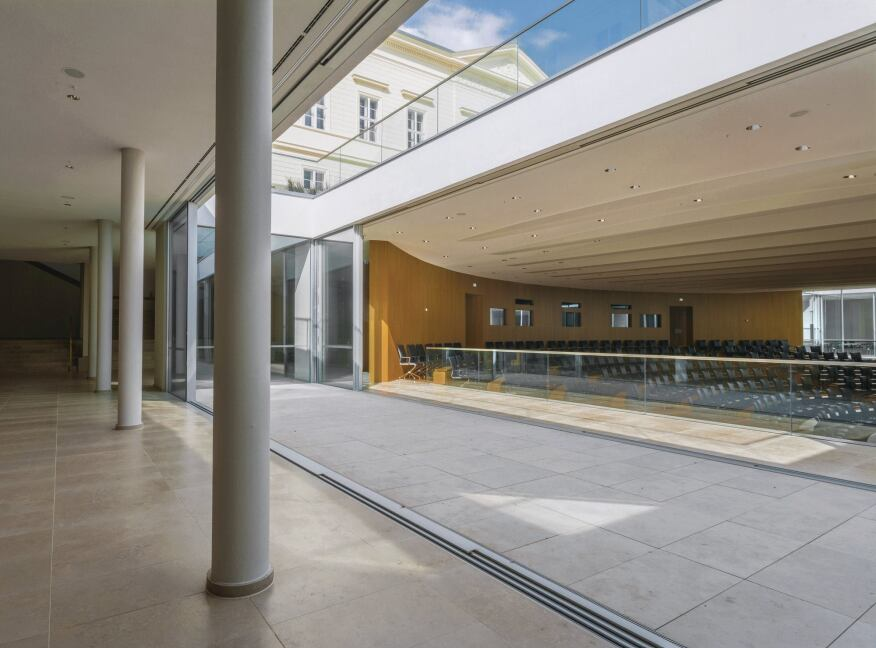 An entirely new below-grade level accommodates a large auditorium and additional seminar rooms. More contemporary than the interiors of the schloss proper, this level is illuminated and ventilated by two atriums cut into the main palace courtyard. Sliding doors connect these open-air spaces to the interiors.