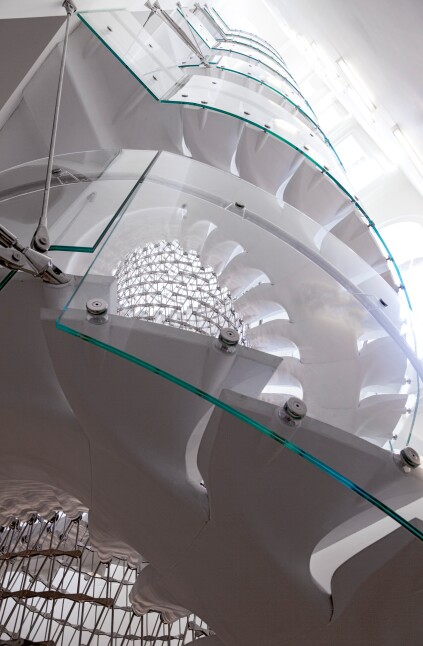 A curved laminated glass balustrade wraps the stair.
