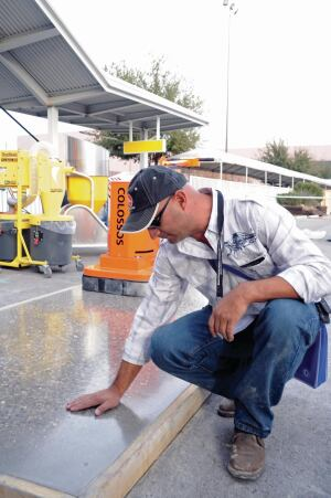 An attendee examines a slab at the Concrete Polishing Demonstration Area.